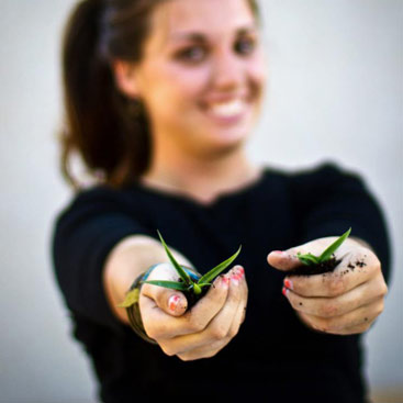 Girl holding plants out in her hands